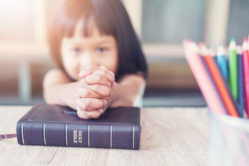 Little Asian girl pray with bible in classroom at school, bible study concept