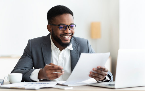 Cheerful black businessman checking reports and making notes