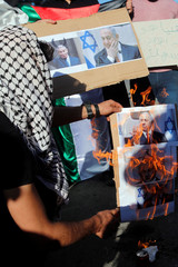 Palestinian demonstrator burns pictures depicting Israeli PM Netanyahu during a protest against the planned visit of Netanyahu to the divided town of Hebron, in the Israeli-occupied West Bank