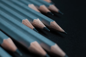 Gray sharpened pencils isolated on black background.