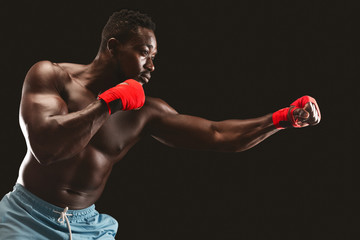 Side view of black fighter making punch over black background