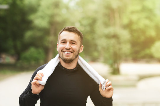 Cheerful man resting after workout with towel around his neck
