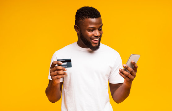 Cheerful black man using credit card and smartphone for purchasing online