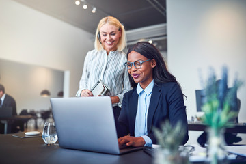 Smiling businesswomen looking at something on a laptop at work