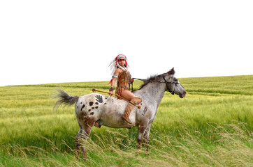 A young Indian woman rides her pony through the prairie grass. She is dressed up in a traditional Indian costume with  a large feather headdress on her head. Behind her a large  prairie wheat field.