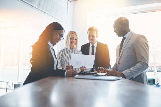 Diverse businesspeople smiling while working together around an