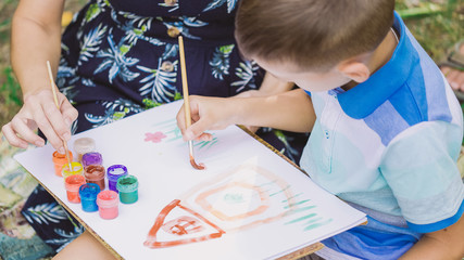 Mother and son painting picture outdoors. Young mom teaching her little son to paint. Baby drawing house and flowers on white sheet of paper. Horizontal color photography.