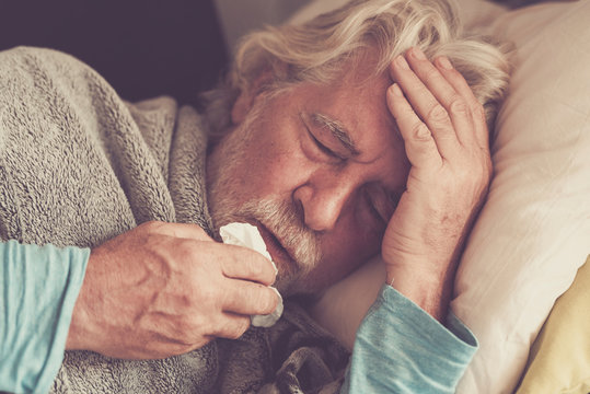 Old people senior man with winter seasonal illness fever cold problems drinking a pharmacy medicine or hot tea to go healthy - concept of mature retired with disease