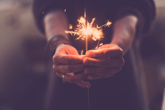 Concept of party nightlife and new year eve 2020 - close up of people hands with red fire sparklers to celebrate the night and the new start - warm colors filter