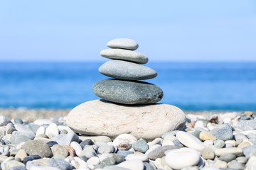 Photo sur Plexiglas Zen pierres a sable balance of stones on the background of the sea and the beach, the concept of harmony and relaxation, close-up
