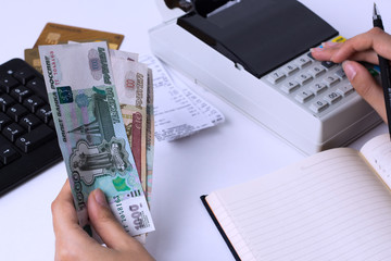 The issue of wages in Russia. Accountant cashier counts the money in rubles and fills the reports and statements. Office worker in the workplace.
