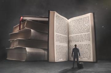 Obraz Surrealistic image of businessman looking at big open book in dark room. - fototapety do salonu