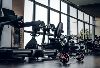 New empty gym club with different type of training apparatuses and big window.