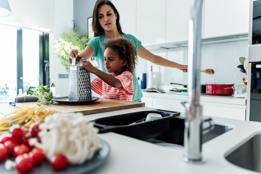 Mother and daughter cooking in kitchen together grating cheese