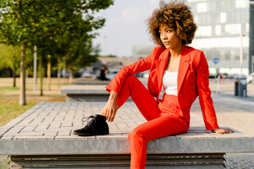 Portrait of young woman wearing fashionable red pantsuit