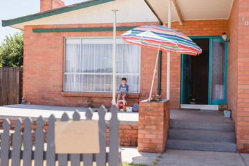 Boy sitting on front porch of home with toy sale sign on fence