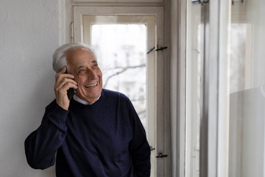 Happy senior man on cell phone at home