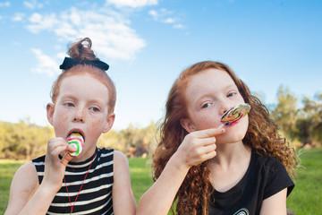 Girls eating rainbow lollipops