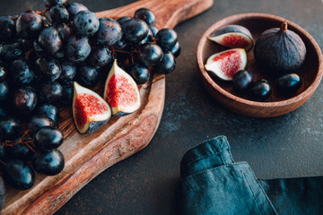 Autumn food still life with season fruits like Bangalore blue grape and figs on a table.