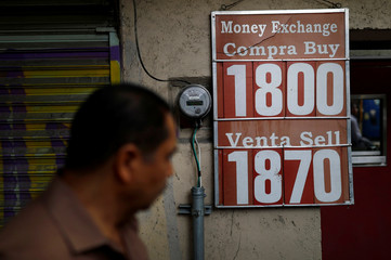 A man walks in front of a board displaying the exchange rate for Mexican Peso and U.S. Dollar at a foreign exchange house in Mexico City