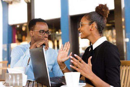 Black  African American coworkers doing digital teamwork arround a coffee cup