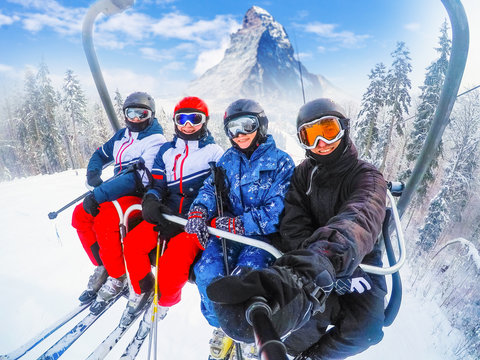 amazing beautiful view ski resort in Switzerland with cable chairlift transport Cheerful young friends skiers on ski lift