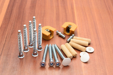 Euro screws, dowels, ties, chrome-plated pipe and console are laid out on a wooden panel