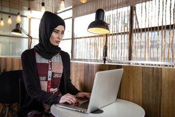 woman working on laptop in cafe with arabic cloth