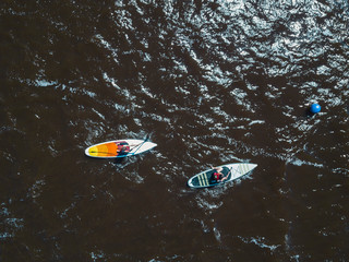 Overhead view of two children paddle boarding
