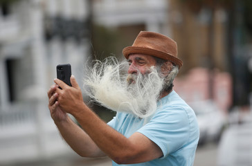 A man's facial hair blows in the wind as he takes a selfie along the waterfront ahead of the arrival of Hurricane Dorian in Charleston