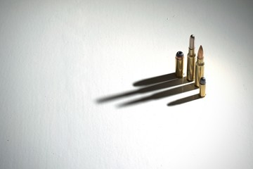 Crime family concept. Several bullets on a white surface with long, dramatic shadows.