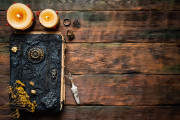 Magic book and magical potion in a vial on a brown wooden table background with copy space.