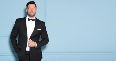 Elegant man in black classic suit posing in nice studio.