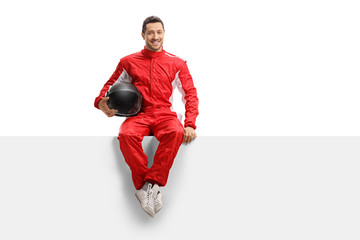 Racer in a red uniform sitting on a panel holding a helmet and smiling Wall mural