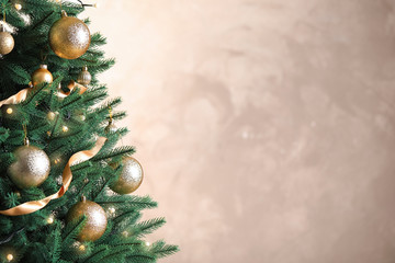Fotobehang Bomen Beautiful Christmas tree with decor on light background. Space for text