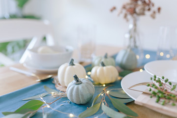 Thanksgiving table decor with white, cream, blue ant teal pumpkins, eucalyptus leaves, string lights, brass kitcheware