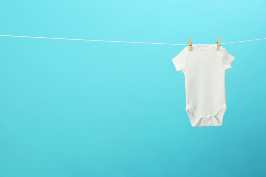 White baby onesie hanging on clothes line against blue background, space for text. Laundry day