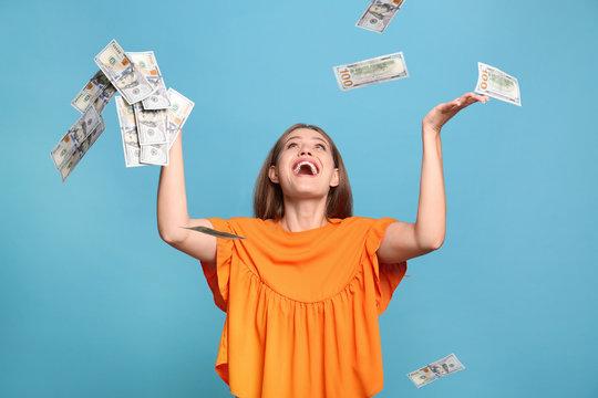 Portrait of happy lottery winner under money rain on light blue background