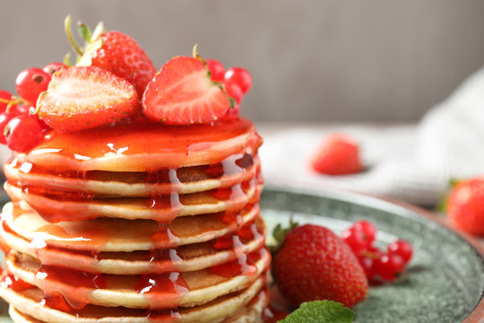 Delicious pancakes with fresh berries and syrup on table, closeup