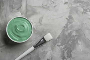 Spirulina facial mask and brush on grey table, flat lay. Space for text