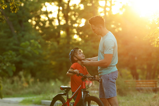 Dad putting bicycle helmet on son in park on sunny day