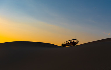 The silhouette of a sand dune and buggy in the Peruvian desert of Ica near the Huacachina Lagoon at sunset in Peru.