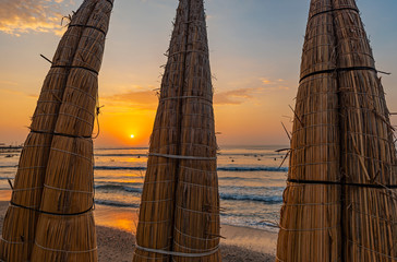 Traditional totora reed boats on Huanchaco Beach at sunset near the city of Trujillo, Peru.