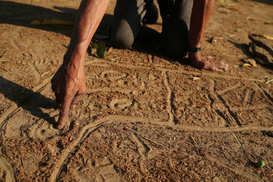 Manoel Kanunxi, chief of the Manoki indigenous people, points to the location of his people's land that was burnt, on a map drawn in dirt, on the outskirts of Brasnorte