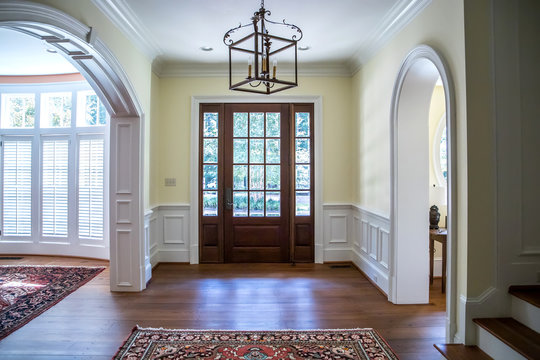 front entrance foyer hallway of a large home house with yellow walls and a wood door with windows and a large custom lighting fixture