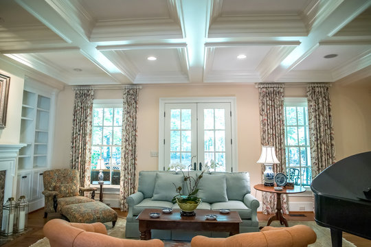 large formal living room in a spacious home. Coffered ceiling and a lot of natural light from the large windows.