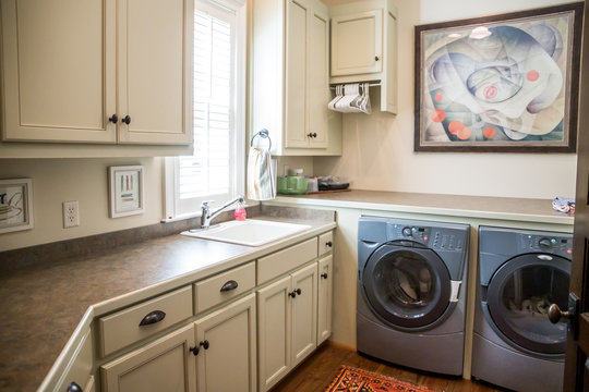 Large cream white laundry room with a window and natural light