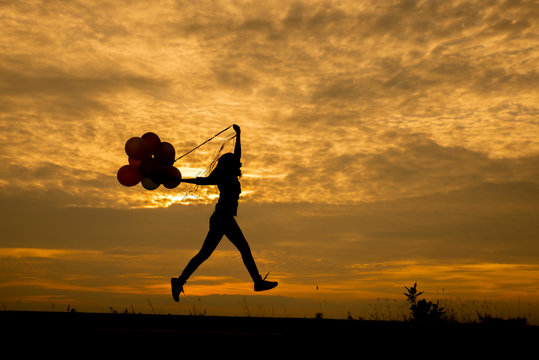 Freedom hand, Release and Let it go concept. Silhouette of a woman jumping with balloons with sunset backgroundThailand. Birthday balloon Holding by Happy Beautiful women in summer carnival