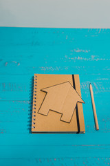 notebook with house made of cardboard, renovation tasks or mortgage budget concept