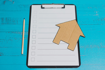 clipping board with blank list and cardboard house, renovation or moving house concepts
